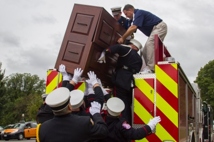 Volunteer firefighters lifted a brown wooden cabinet holding 87 U.S. flags. The flags will be given to family members of fallen firefighters Sunday in Emmitsburg, Md. SHFWire Photo by Matias J. Ocner